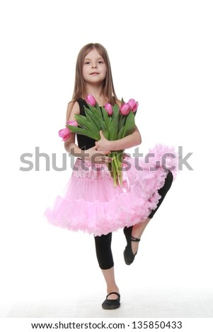little dancer with long blond hair holding a beautiful bouquet of pink tulips - stock photo