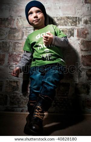 Little dandy posing against brick wall - stock photo