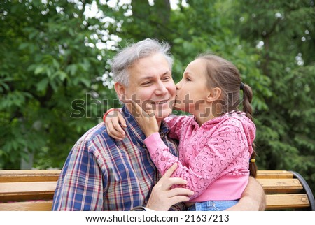 Little daughter kissing her father in park - stock photo