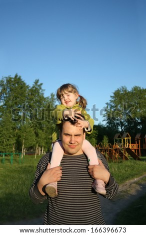 Little daughter sits on shoulders of father and keeps his head outdoors. - stock photo