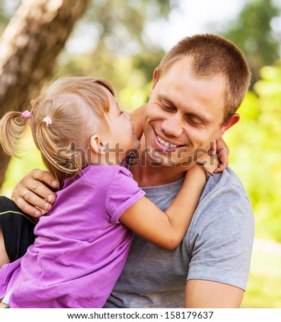 Little daughter try to kiss her father - stock photo