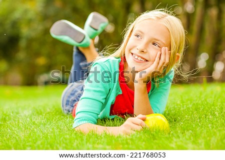 Little day dreamer. Cute little girl leaning head on hand and looking away with smile while lying on the green grass  - stock photo