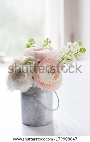 Little delicate elegant bouquet of flowers, buttercups and white lilacs in tin can on white wooden table, interior decoration - stock photo