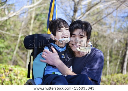 Little disabled boy in wheelchair hugging older brother outdoors, smiling together. Child has cerebral palsy. - stock photo