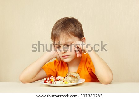 Little displeased boy does not want to eat a pasta with cutlet  - stock photo