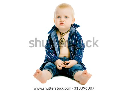 Little dissatisfied boy in a plaid shirt, tie and jeans on a white background - stock photo