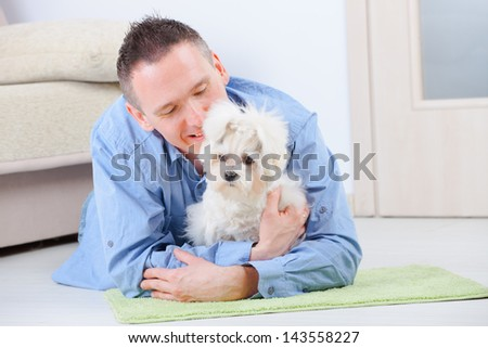 Little dog maltese laying with his owner on the floor in home - stock photo