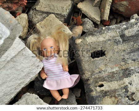 little doll lies among the wreckage of the house - stock photo