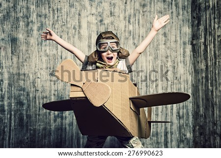 Little dreamer boy playing with a cardboard airplane. Childhood. Fantasy, imagination. - stock photo