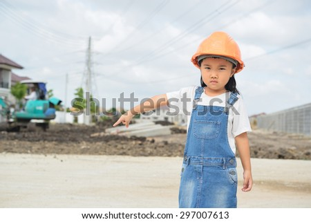 Little engineer inspecting her work in building site - stock photo