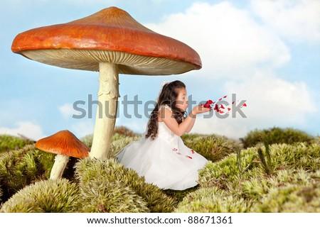 Little fairy girl blowing rose petals under a toadstool umbrella - stock photo