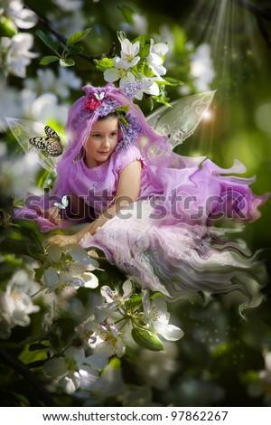 Little fairy girl on the blossom cherry branch - stock photo