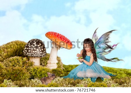 Little fairy girl with wings putting a crown on a green tree frog - stock photo