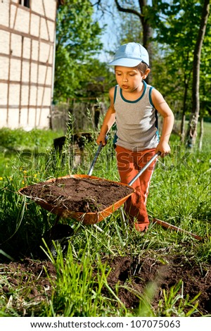 Little farmer moves a heavy wheelbarrow full of earth - stock photo