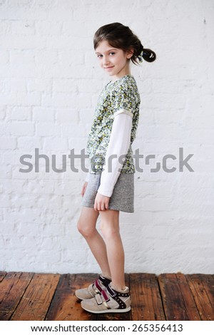 Little fashion girl in fashion  clothes posing over white brick background - stock photo