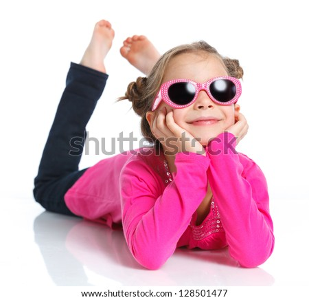 Little fashion girl lying in pink dress and sunglasses. Isolated white backround. - stock photo