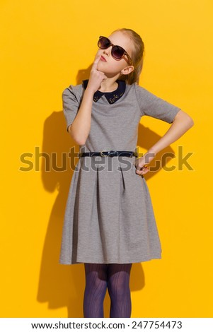 Little fashion model thinking. Girl in sunglasses and gray dress thinking and looking up. Three quarter length studio shot on yellow background. - stock photo