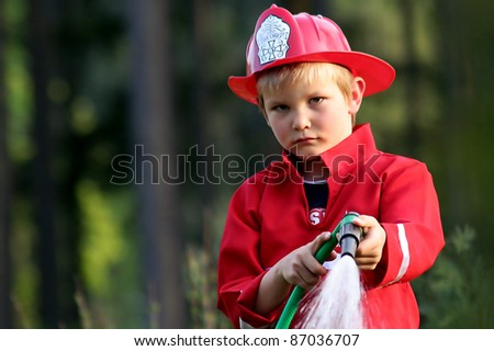 little fire man in the garden with the water hose - stock photo