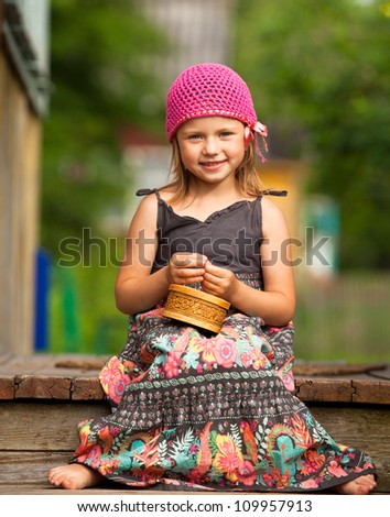 Little five-year girl on the porch of a village house. - stock photo