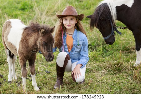 Little foal - cute girl takes care of the pony foal - stock photo