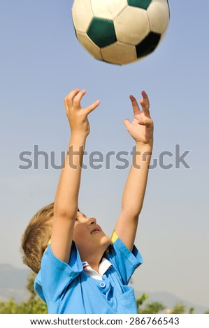 Little football player catches a ball arms, which is highly threw his father - stock photo