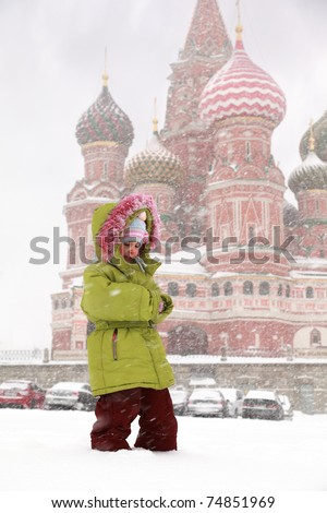 Little frozen girl standing in front of St. Basil's Cathedral in Moscow, Russia at wintertime during snowfall - stock photo