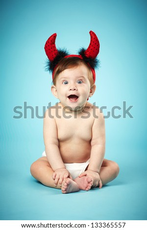 little funny baby with devil horns on blue background - stock photo