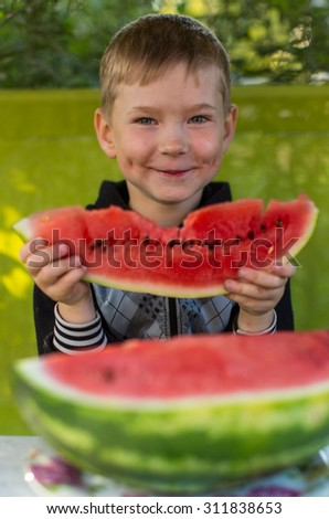 Little funny boy eating watermelon. - stock photo