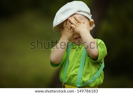 little funny boy plays hide and seek - stock photo
