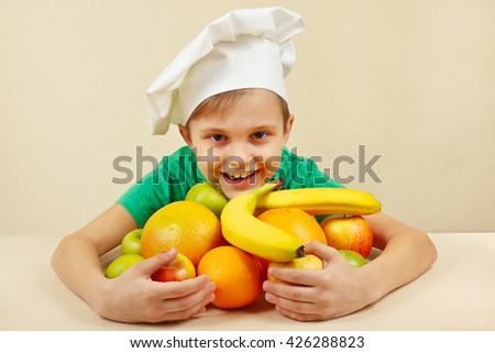 Little funny boy with fruits at the table - stock photo