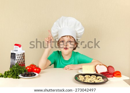 Little funny chef at the table with ingredients for pizza - stock photo