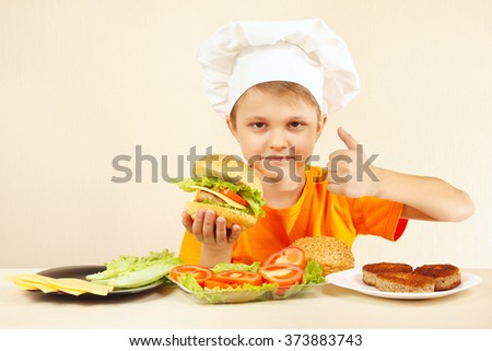 Little funny chef expressive enjoys a cooked hamburger - stock photo