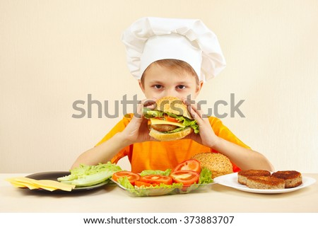 Little funny chef is tasting the cooked hamburger - stock photo