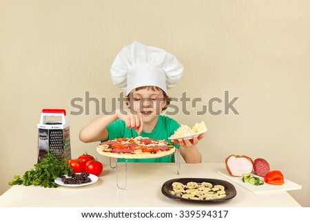 Little funny chef puts a grated cheese on the pizza crust - stock photo
