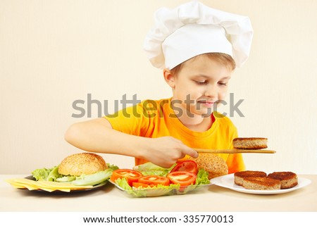 Little funny chef puts meat on the hamburger - stock photo