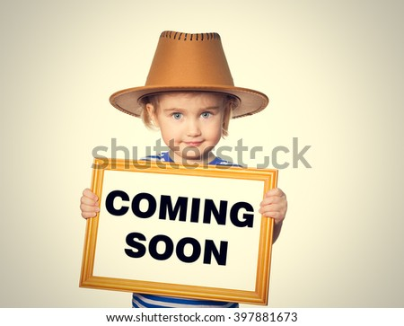Little Funny girl in striped shirt with blackboard. Text  coming soon.  Isolated on gray background. - stock photo