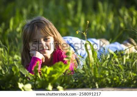 Little funny girl lying in the green grass. - stock photo