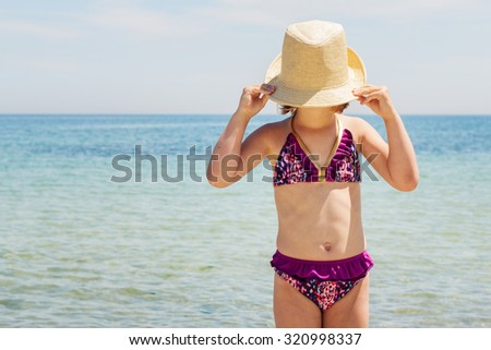 Little funny girl on the beach in a hat. Selective focus. - stock photo