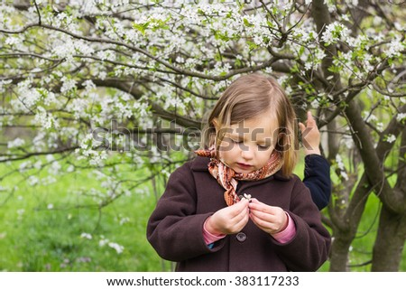 Little funny girl (4 years) near flowering trees. - stock photo
