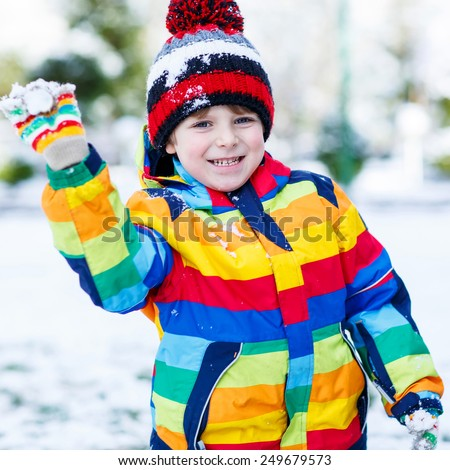 Little funny kid boy in colorful winter clothes having fun with playing with snow ball fighting, outdoors. Active outdoors leisure with children in winter. Kid with warm hat and gloves - stock photo