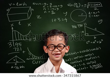 Little genius Asian student boy with glasses smiling over green chalkboard with math equivalents written on it - stock photo