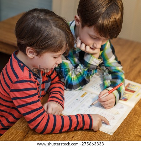 Little genius boy help his brother with homework, problem solving, education - stock photo