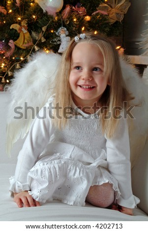Little girl acting as an christmas angel. Christmas tree in a background. - stock photo