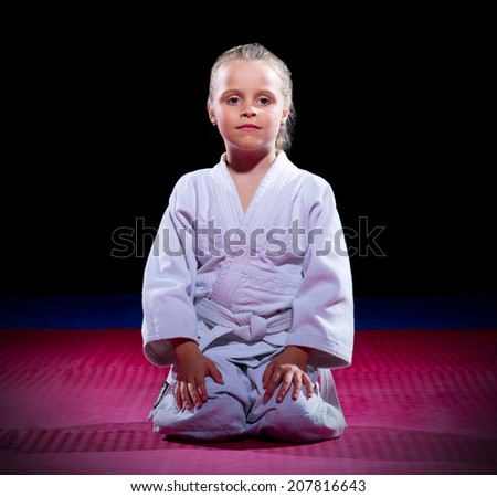 Little girl aikido fighter on black - stock photo
