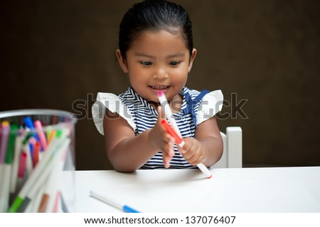 Little girl amazed and playing with colorful markers on a white table - stock photo