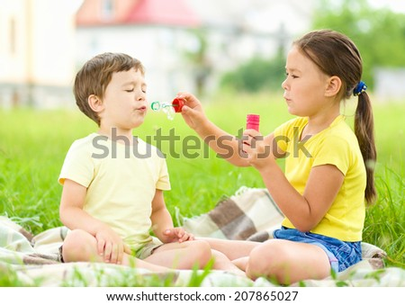 Little girl and boy are blowing soap bubbles, outdoor shoot - stock photo