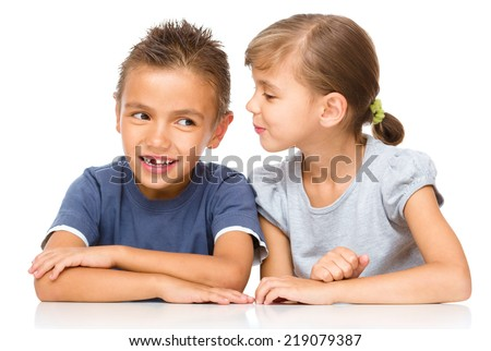 Little girl and boy are whispering in ear, isolated over white - stock photo