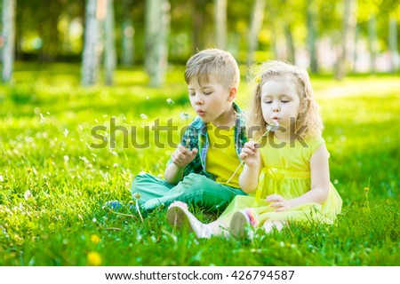 Little girl and boy blowing dandelion together - stock photo
