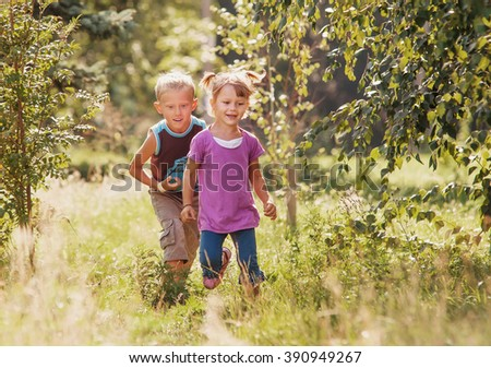 Little girl and boy playing together in sunny summer garden - stock photo