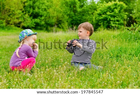Little girl and boy playing with binoculars sitting in a green grassy field as they enjoy an educational day exploring and learning about nature - stock photo